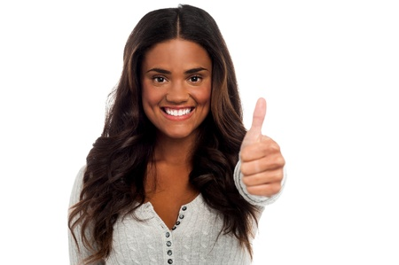 yup: Smiling young woman showing thumbs up isolated over white