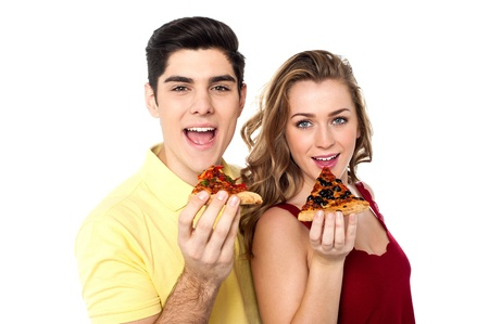 relishing: Boy and girl each holding slice of yummy pizza