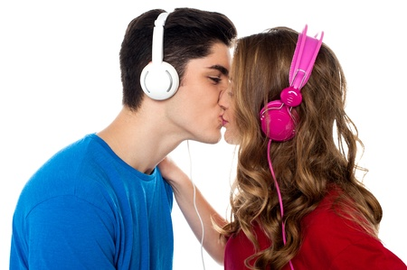Love couple tuned into musical world and kissing each other Stock Photo