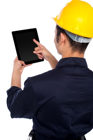 Young construction worker operating touch pad device photo