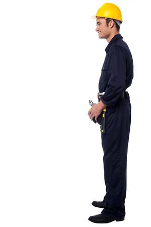 side pose: Trabajador de construcci�n sonriente feliz celebraci�n de la pose de herramientas lateral