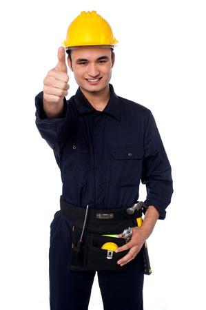 protective helmets: Bel uomo in casco giallo di sicurezza e costruzione lavoratore uniforme