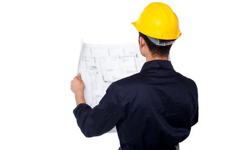 ingeniero civil: Ingeniero de revisar el plan de obra de construcci�n civil de sexo masculino joven Foto de archivo