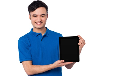 Young handsome guy presenting brand new tablet device photo