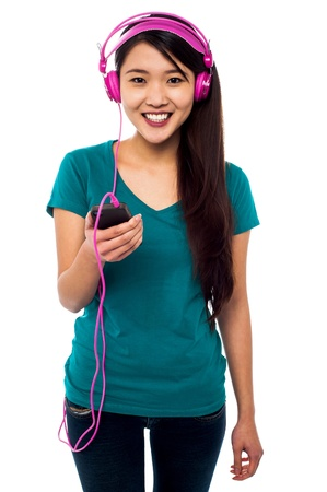 audio player: Girl listening to music with headphones wired into audio player
