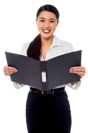 Young smiling chinese businesswoman reviewing employee records photo
