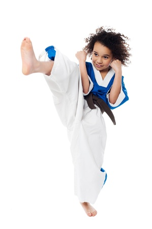 Young kid kicking in the air while practicing karate photo