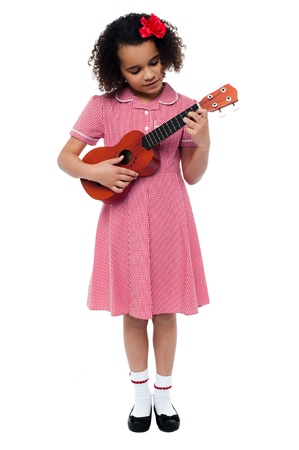 Funny little girl with a guitar isolated on white photo