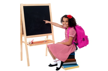 Pretty school girl sitting on stack of books and pointing towards blank chalkboard photo