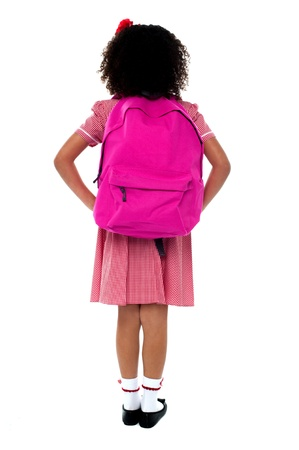 pretty little girl: Primary school girl in uniform with school bag over shoulder over white