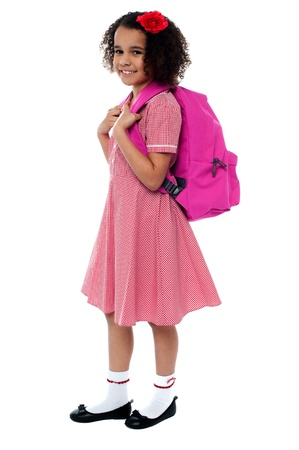 Curly haired school girl in uniform carrying pink backpack on shoulders photo