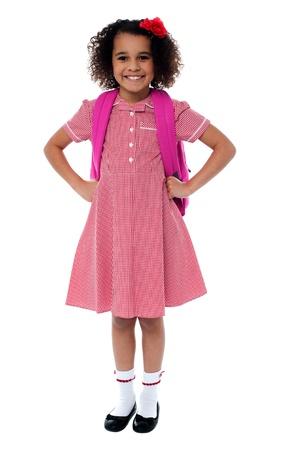 zapatos escolares: Segura chica linda de la escuela en uniforme con mochila de color rosa con las manos en la cintura Foto de archivo