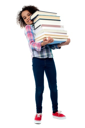 Little girl holding pile of school books grinning happily photo