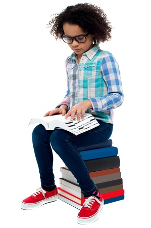 Kid wearing spectacles sitting on stack of books and learning Stock Photo - 20465087