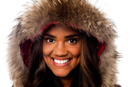 Closeup of a sweet smiling girl wearing furry hood winter jacket photo