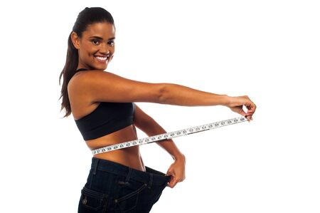 losing control: Young woman measuring waist with a white measuring tape Stock Photo
