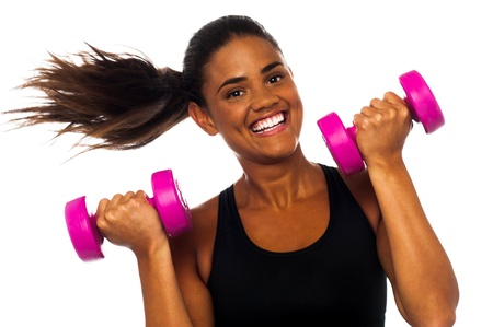 Cheerful woman exercising and building up biceps using dumbbells photo