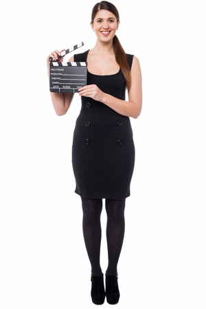 Isolated smiling young girl posing with clapboard photo