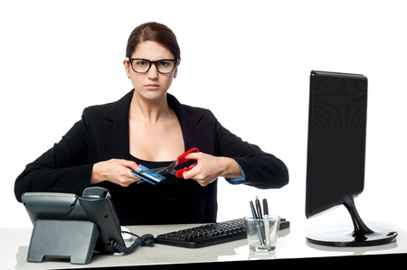 Young professional female cutting her credit card with scissors photo