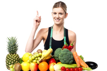 Attractive girl raising her arm. Standing behind bunch of fruits and vegetables photo