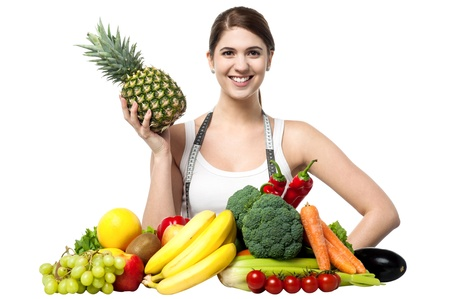 Fit pretty smiling female holding pineapple in one hand and posing photo