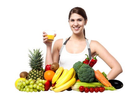 Beautiful young woman with fruits and glass of juice photo