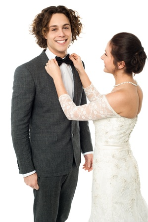 Attractive young bride adjusting the bow tie of her man photo