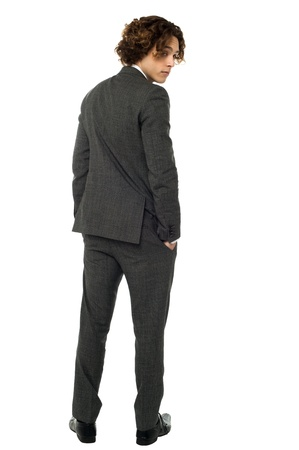 Smart young man in tuxedo turning back photo