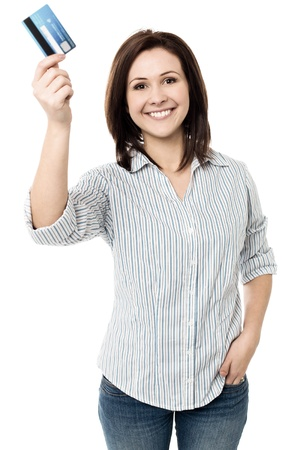 Young smiling woman showing her credit card to the camera