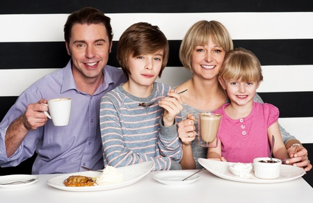 Happy family of four enjoying breakfast at a restaurant photo