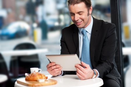 Corporate male manager reviewing business updates on tablet pc while waiting for his order photo