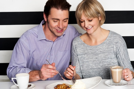 Beautiful middle aged couple enjoying coffee and trying new cuisine photo