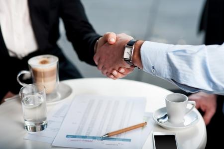 Twee business tycoons ontmoeten met een kop koffie en gesloten langlopende deal Stockfoto