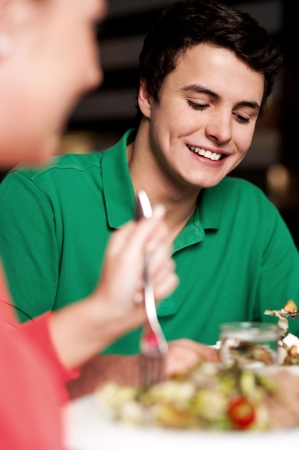 relishing: Boy in focus enjoying his meal. Having great time. Blur image of a woman too Stock Photo