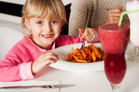 Cute girl kid enjoying meal in restaurant with her mother. Cropped image photo