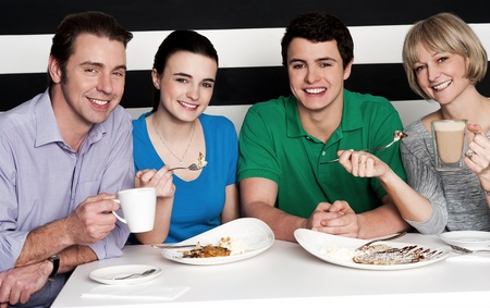 Cheerful family of four relishing nice cuisine breakfast and chocolate shake photo