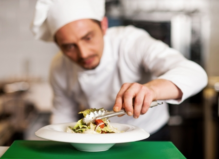 preparing food: Salad is ready to be served. Chef ding last second decoration Stock Photo