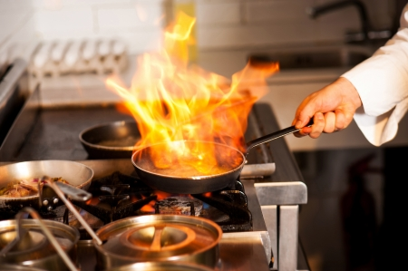부엌 난로에 프라이팬에서 불꽃과 함께 요리 요리사