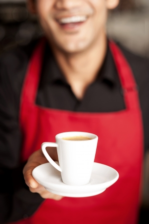Cheerful shop owner serving freshly brewed coffee to you photo