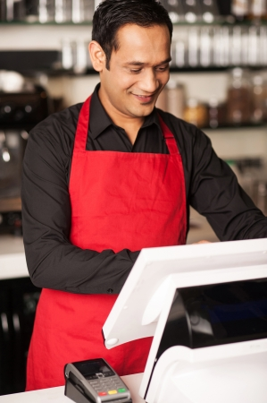 billing: Cheerful barista staff cross-checking the order before billing the same
