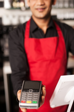 Cropped image of barista staff offering card swipe service to accept payment photo