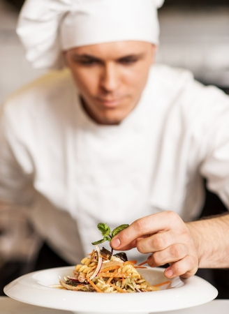 Handsome male chef dressed in white uniform decorating pasta salad