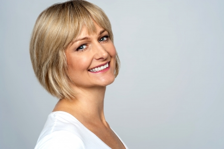 side pose: Pretty middle aged lady posing over grey background