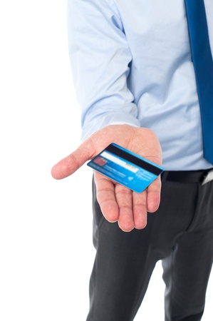 Young corporate man showing his credit card to the camera photo
