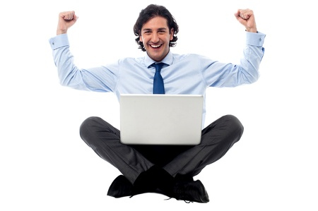 legs crossed: Young excited businessman with laptop sitting on floor Stock Photo