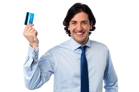 Smiling young corporate man holding up his credit card photo
