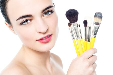 Portrait of a beautiful girl with makeup brushes photo