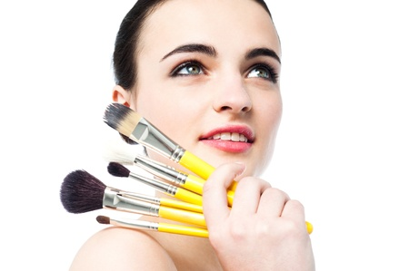 Portrait of beautiful girl with brushes for make-up photo