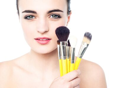 Glamorous girl with makeup brushes near her face photo