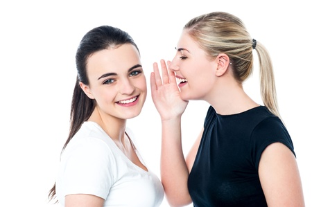 hearsay: Two beautiful smiling girls sharing a secret Stock Photo